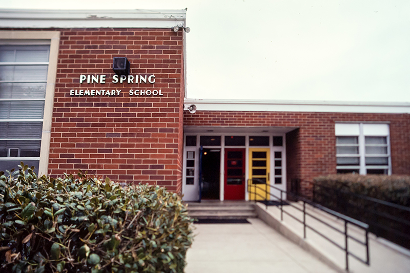 Undated color photograph of Pine Spring Elementary School's main entrance. The front doors are painted white, blue, red, and yellow.